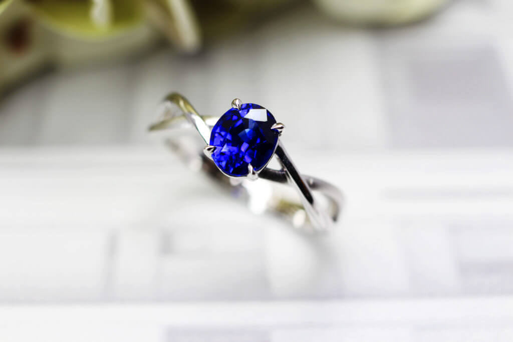 Customised Proposal Ring with vivid blue sapphire coloured gemstone. Designed with twisted band from sketch and handcrafted to final piece | Local Singapore custom made jeweller in wedding jewellery and proposal ring for engagement with coloured gemstone and diamond.