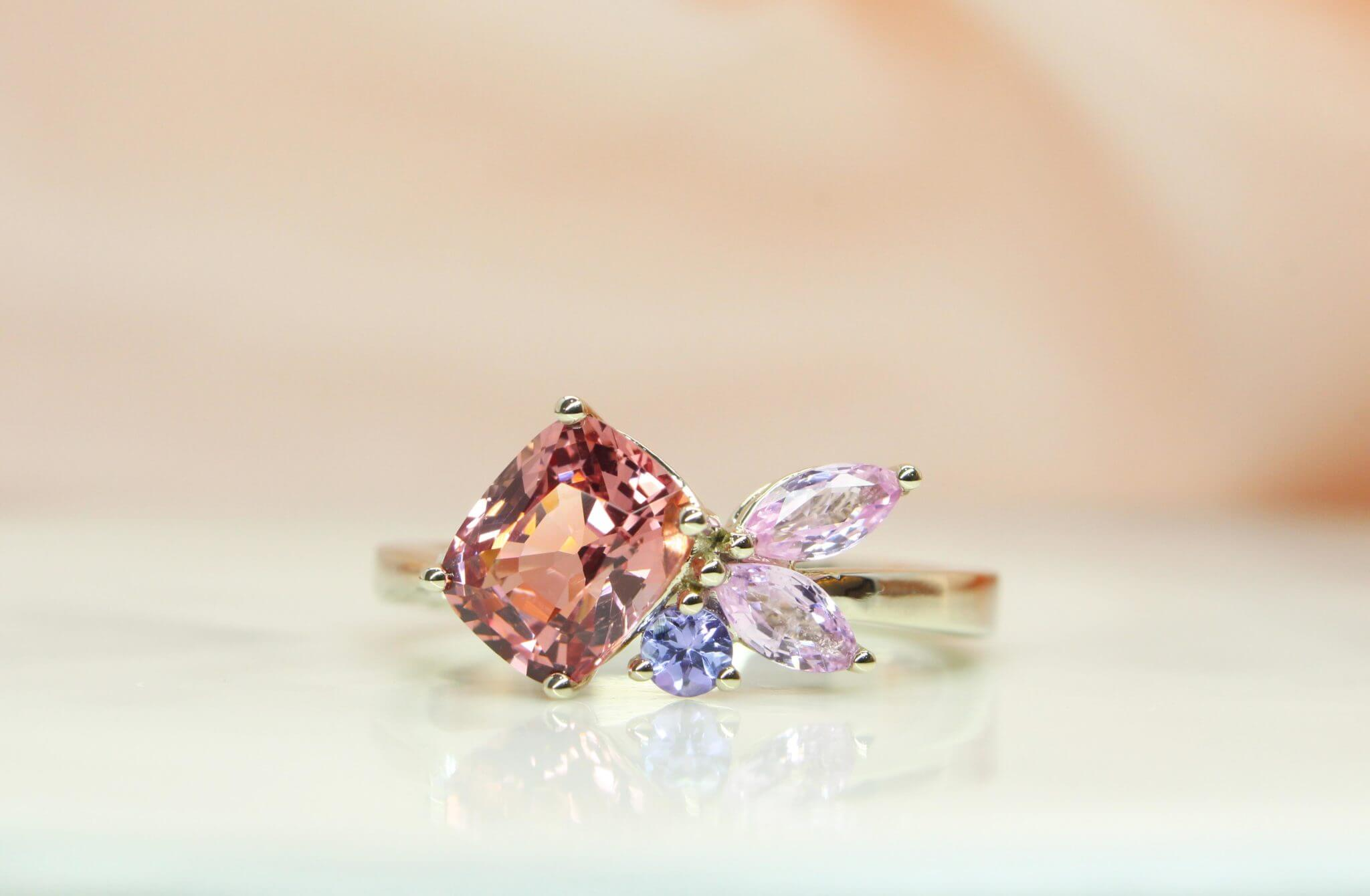 Cluster ring with spinel in orange pink shade instead of the classic solitaire for their wedding engagement, crafted in natural white gold band | Local Singapore Customised Jeweller in Wedding and Engagement ring with coloured gemstones.