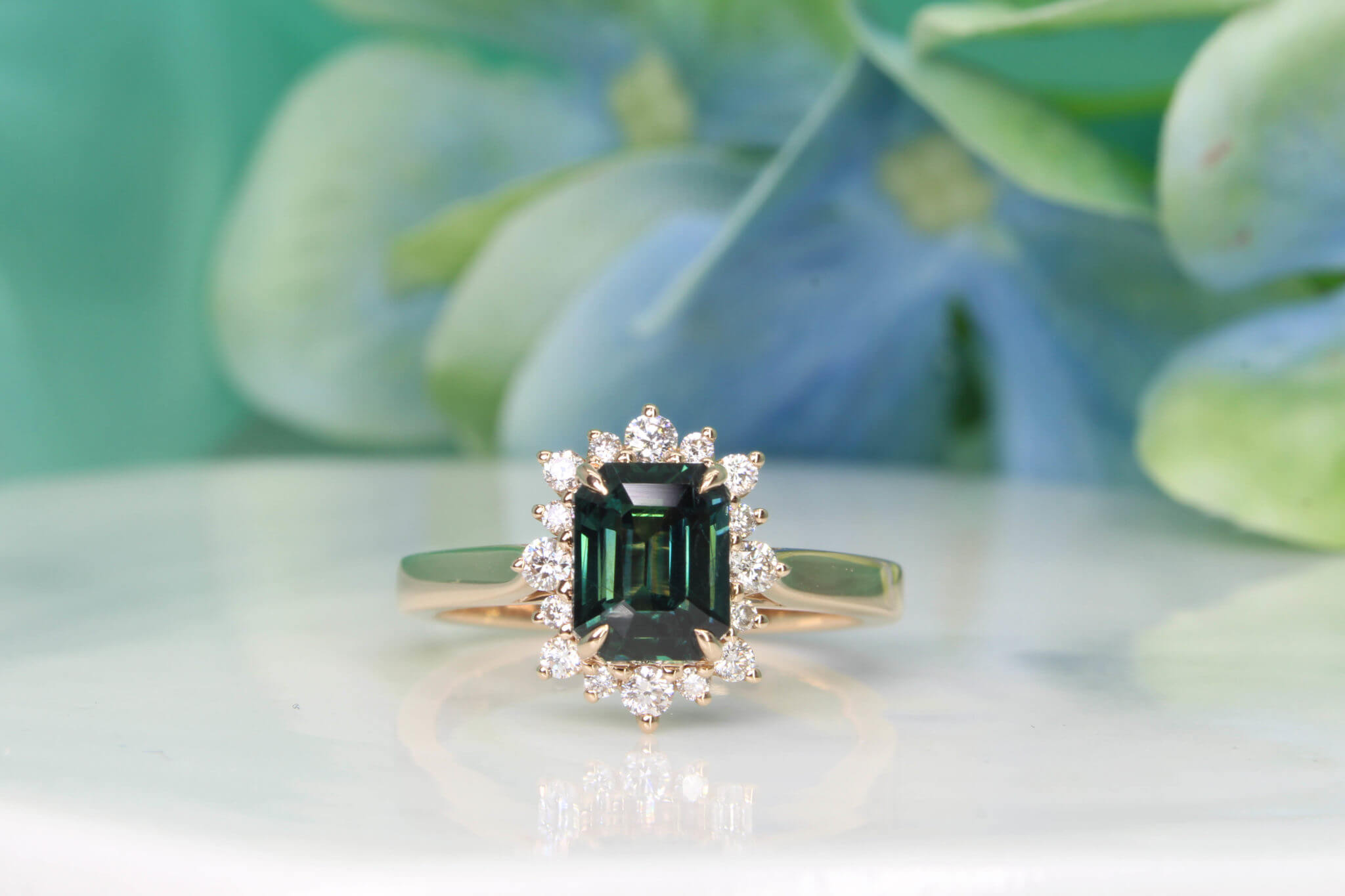 Teal Sapphire Engagement ring customised with alternate sizes diamond, gives a star burst look to the overall design.Crafted in 750 18k Rose gold bands, regal and radiant, this exquisite engagement ring was crafted to perfection | Customised Engagement Ring Teal Sapphire Singapore