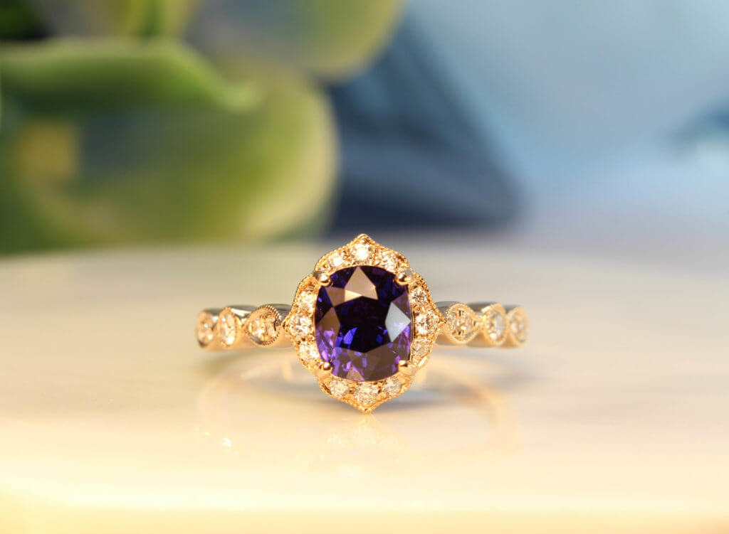 Art deco Proposal Ring with colour change sapphire, surrounded with diamonds to impart a floral and feminine look to this design. This design exudes an overall vintage art deco look with its mil-grain design | Local Singapore Private Jeweller in customised proposal ring.