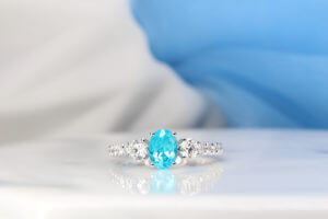 Brazilian Paraiba Tourmaline is a fascinating rare gem that exhibits a sensational colour shade. The unique colour shade of a Brazil Paraiba make it of the rarest gem on world which is priced much more than a diamond. This customised engagement ring is customised with side round diamonds and a pave of 3/4 diamonds.