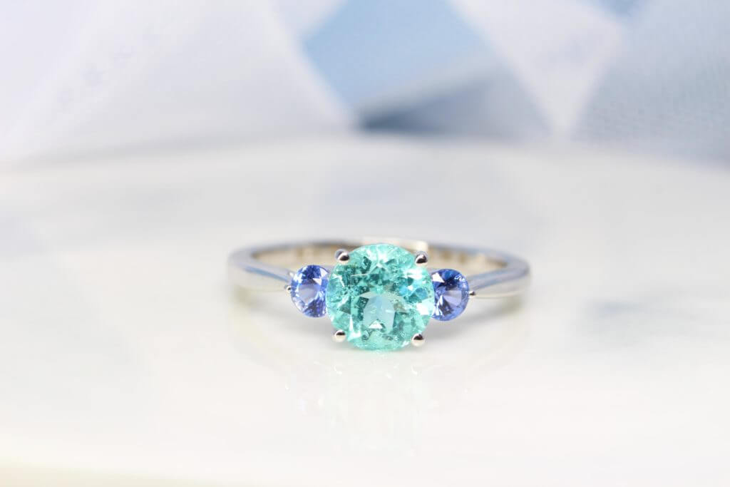 Engagement Ring with Paraiba Tourmaline customised with round blue tanzanite gemstone in 750 white gold band, unique customised engagement ring without diamond but customised with coloured gemstone for one of a kind design Local Singapore Jeweller in customised engagement ring with paraiba tourmaline gemstone.