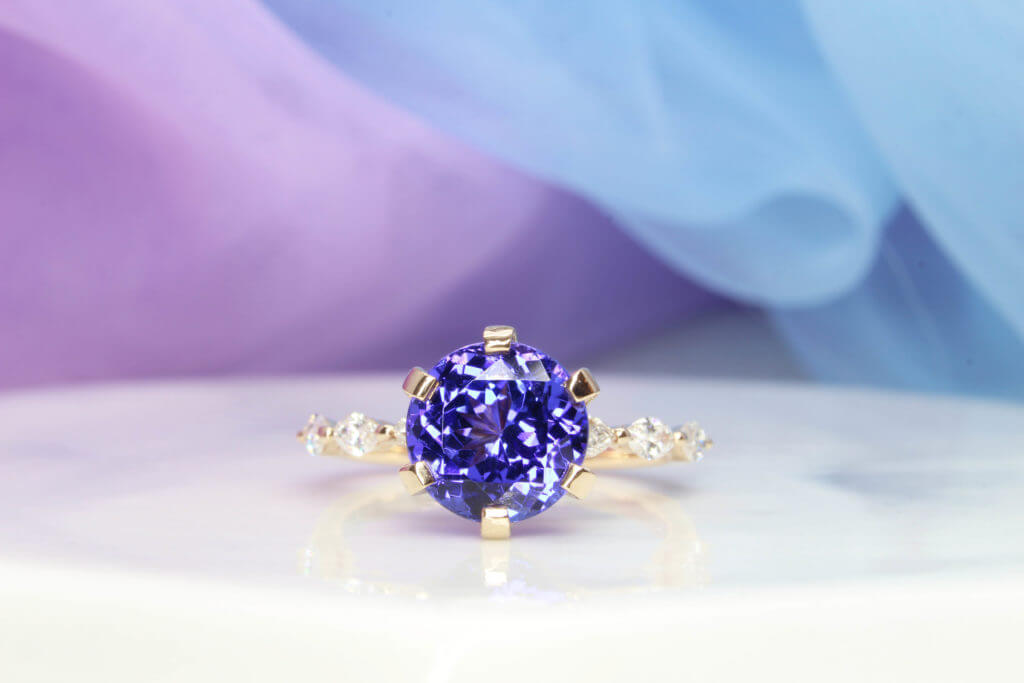 Tanzanite Wedding Rings customised with round brilliance tanzanite in six prongs ring setting with marquise and round diamonds on side bands - Proposal & Wedding Bands customised to complement the proposal ring | Local Singapore Jeweller in customised jewellery with Tanzanite and coloured gemstone