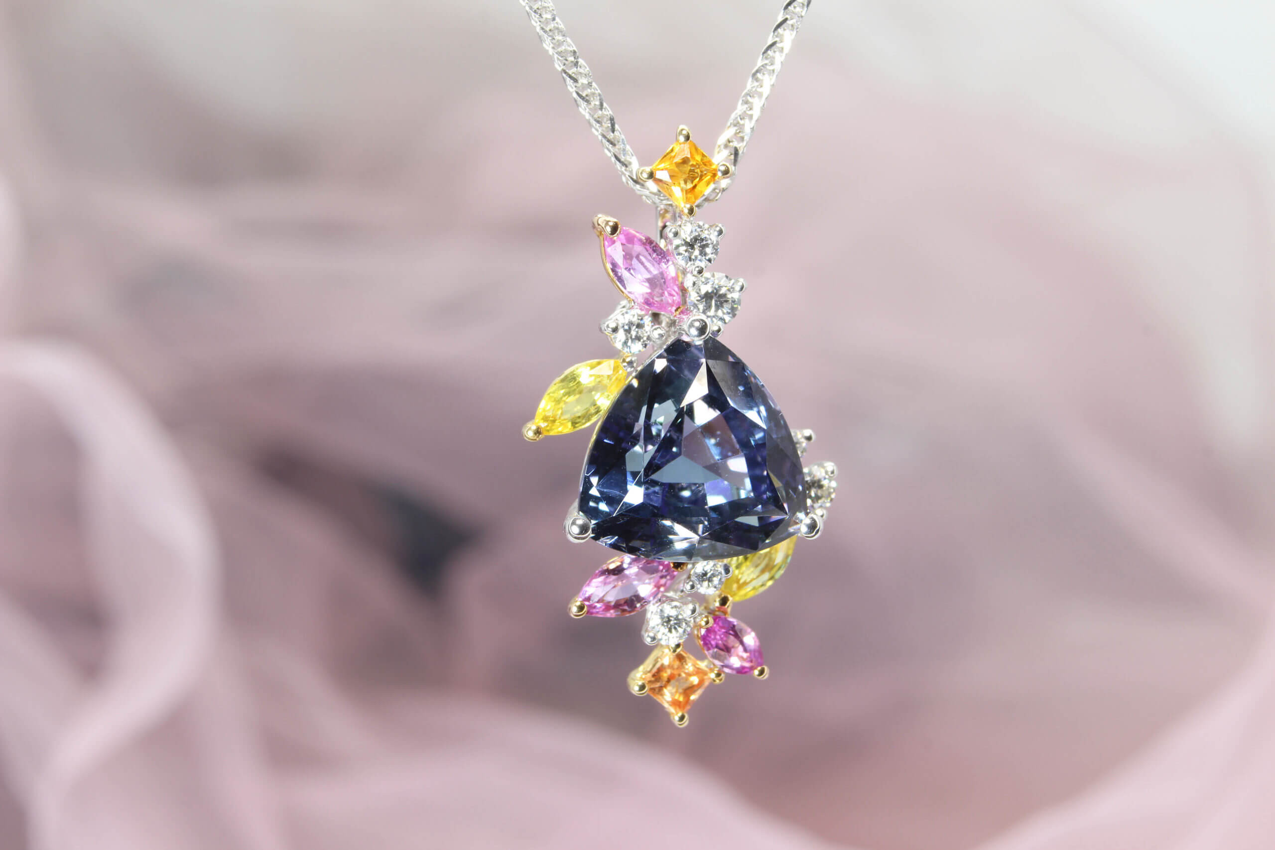 Tanzanite Pendant in unique trilliant shape customised with multiple coloured sapphire gemstone from pink, yellow to orange shade. The flora-style cluster of multi-shaped and colourful gemstones. Local Singapore Jeweller in customised jewellery and Wedding Jewellery with coloured gemstone.