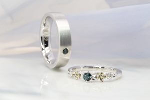 wedding bands customised to flora design with teal spinel