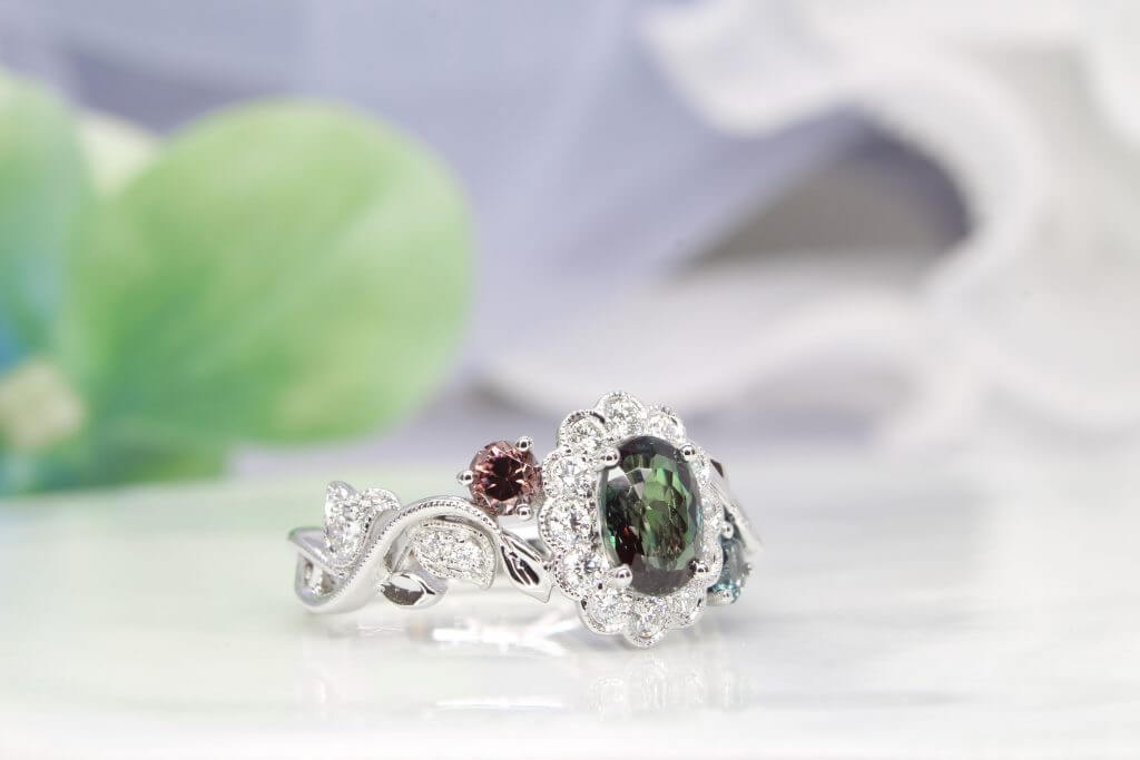 Alexandrite gem appears green under daylight and reddish-purple under incandescent light, colour change phenomenon. Customised flora ring with halo diamonds set around the alexandrite, resemble a flower design. Customised Jewellery with colour change alexandrite jewellery in Singapore