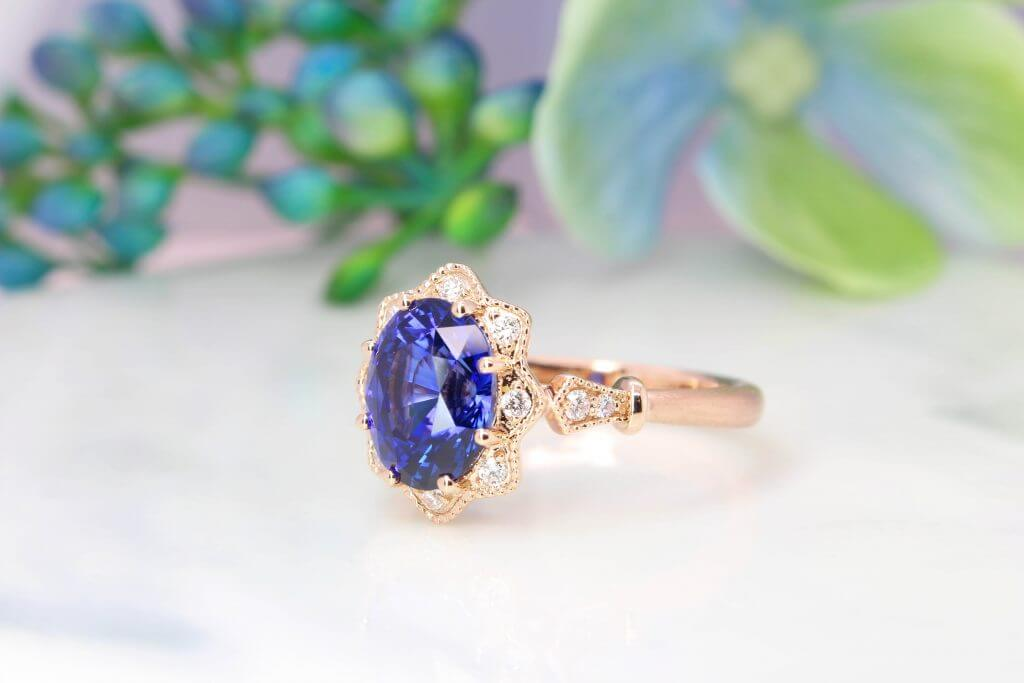 Vintage Floral Sapphire Ring with Halo Diamond - Customised Engagement Ring showcasing vivid blue oval natural sapphire gemstone. Custom made in rose gold band, the fine milgrain detailing has a vintage vibe flowing from each part of the ring. Customised Jewellery for wedding engagement in Singapore
