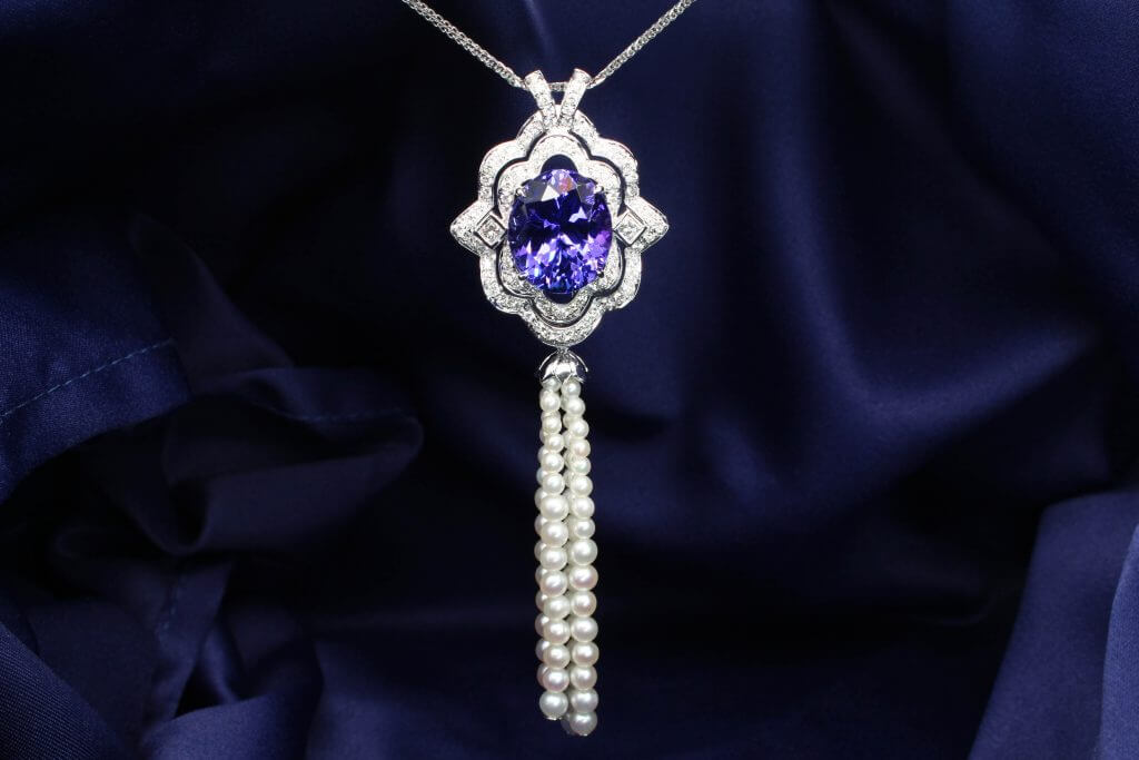Featuring an exceptional Art Deco jewel is a breath-taking piece of statement jewellery. Center gem is a vivid violetish blue tanzanite in an oval design with an art deco symmetrical and geometric look. Tanzanite chosen to be the birthstone gem for the month of December. Bespoke fine jewellery in GIOIA Fine Jewellery.