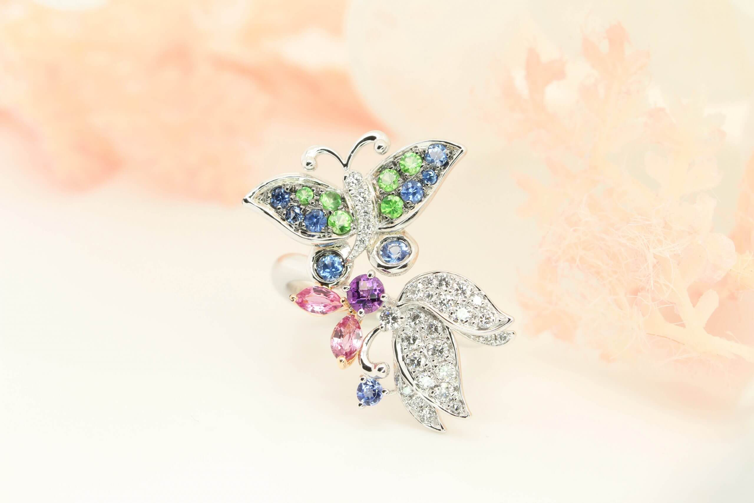 Customised ring bearing a butterfly theme symbolises feminism and the inherent beauty of the person. Butterflies symbolise transformation in life and are believed to bring serenity and happiness to life. The fine detailing and delicate design make this natural inspired design fine jewellery with coloured gemstone special and one of a kind.