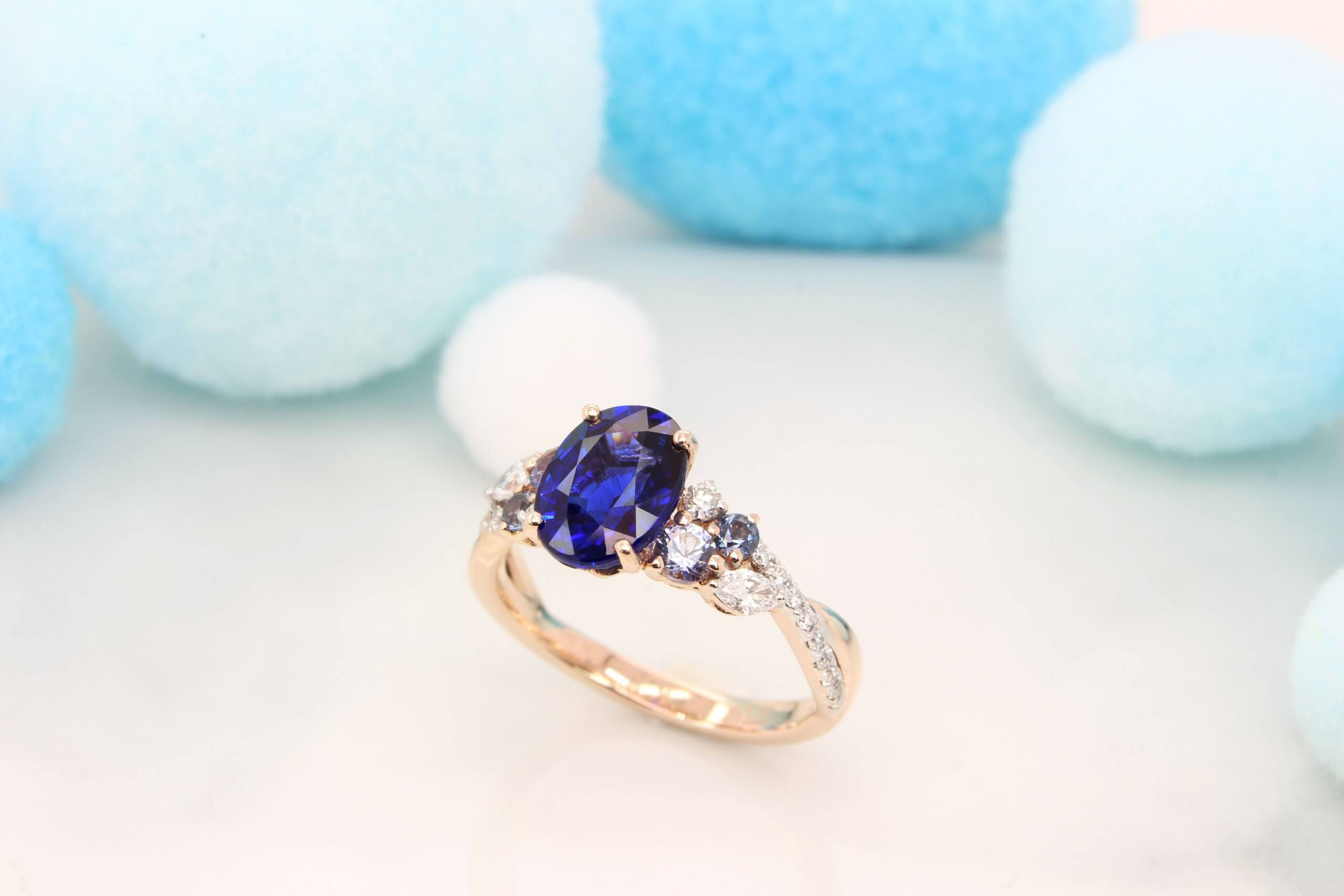Featuring a vivid blue sapphire gem with cluster blue spinel and marquise shaped diamond design. Exceptional Sapphire engagement ring customised unique design.